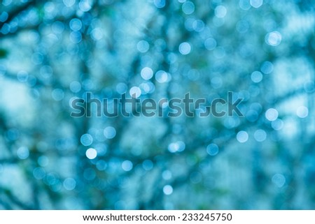 Defocused holiday background with blue tones and sparkle circles and tree lines - stock photo