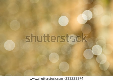 Defocused holiday background with gold tones and sparkle circles - stock photo