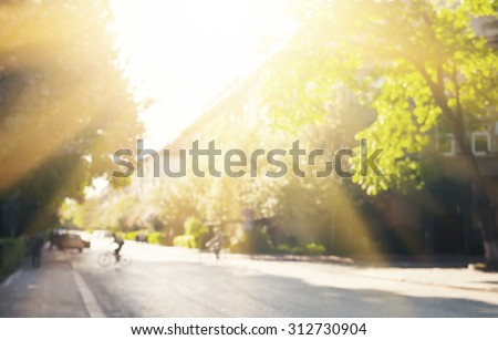 Defocused image of street with trees and sunlight - stock photo