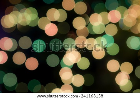 Defocused light green and brown bokeh glowing in the dark for holiday, Christmas and celebration for abstract background - stock photo
