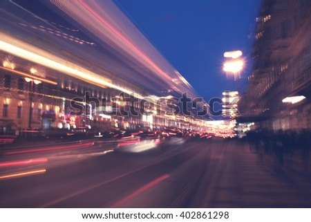defocused night city life: cars, cyclist and street lamps. white nights in St. Petersburg, Russia - stock photo