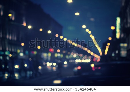 defocused night city life: cars, people and street lamps, retro style - stock photo