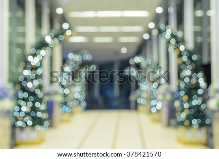 Defocused office, hotel lobby or shopping mall building indoor background with Christmas light illuminated on tree - stock photo