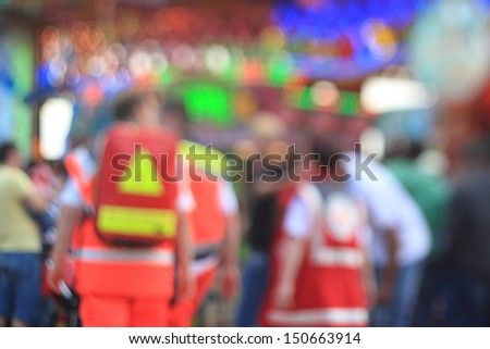 defocused photo of emergency medical services personell at funfair - stock photo