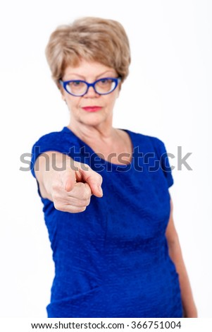 Defocused senior woman pointing with finger at you, looking at camera, white background