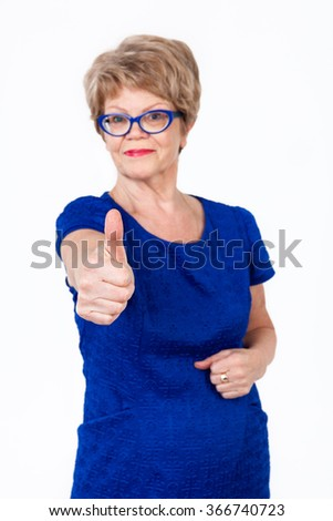Defocused senior woman weared blue dress showing thumb up gesture, white background