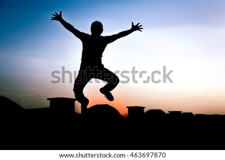 Defocused Silhouette of a boy is jumping over beautiful sunset background.