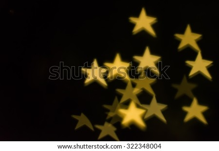 Defocused star bokeh on Christmas light.Star bokeh lights on black background. - stock photo