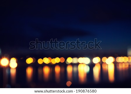 defocused street lamps and reflection on a water, night city life - stock photo