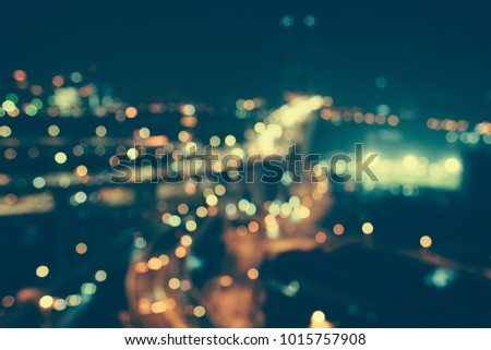 Defocused urban abstract texture bokeh city lights & traffic jams in the background with blurring lights on the top of mountain.