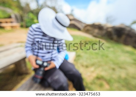 Defocused woman take a photo on landscape background.
