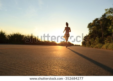 defocused young fitness woman running on sunrise seaside trail