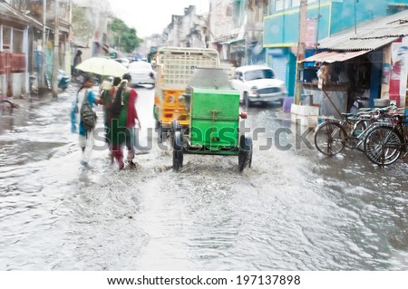 Defocussed view of flash flood at Indian city street with auto rickshaw, bicycles and pedestrians after monsoon rain. India, Tamil Nadu - stock photo