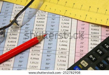 Degrees and radians mathematical table together with glasses, red pencil, measurement and calculator - stock photo