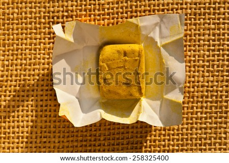 Dehydrated condiment bouillon stock cube salty meat and vegetables aromatic yellow spice, ingredient single whole portion wrapped and open in paper pack on mat, hard daylight, view from above.