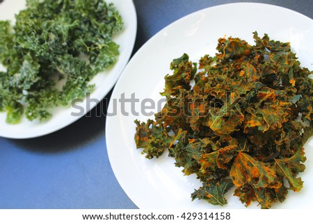 Dehydrated kale chips, white sour cream and onion and orange curry flavours - raw vegan healthy food