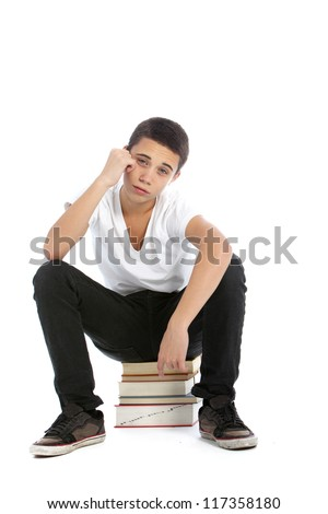 Dejected teenaged boy sitting on top of a pile of his textbooks with a despondent expression isolated on white