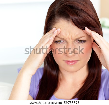 Dejected woman having a headache sitting in the living-room at home