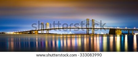 Delaware Memorial Bridge by night, viewed from New Jersey. The Delaware Memorial Bridge is a set of twin suspension bridges crossing the Delaware River between the states of Delaware and New Jersey - stock photo