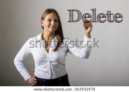 Delete - Beautiful girl writing on transparent surface - horizontal image