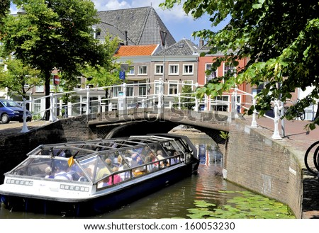 DELFT,HOLLAND-JULY 18,2010;Tourist sight seeing boat nearing a bridge over a canal. July,18,2010 Delft,Holland - stock photo