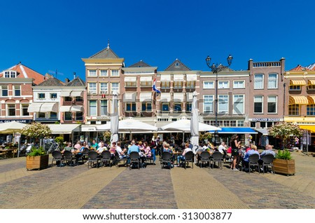 DELFT,THE NETHERLANDS - APRIL 16: Tourists in City of Delft on April 16, 2014 , the Netherlands. Delft is known for its historic town centre with canals and a popular touristic destination.