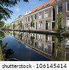 Delft, The Netherlands: church towers and houses reflected in canals on a beautiful summer day - stock photo