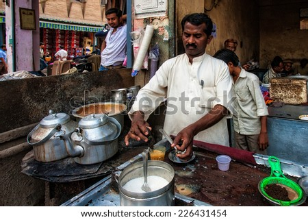 DELHI - APR 16: Unidentified Indian man preparing tea on April 16, 2011 in Delhi, India. Delhi is the largest urban agglomeration in India, and the 4th most populous city on the planet. - stock photo