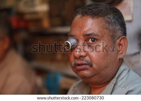 DELHI,INDIA - APRIL 3,2013 : Unidentified watchmaker with a magnifier in his eye repairs clocks in the streets of Delhi,India.