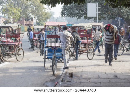 DELHI INDIA - DEC 20 :  crowd and rickshaw driver near old delhi railway station. this area is in old delhi, old delhi is aged and famous place of Delhi on december, 20, 2014, india - stock photo