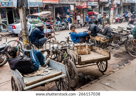 DELHI , INDIA - JANUARY 24: Bicycle rickshaw porters waiting for work in a side street on January, 24 2015 in Old Delhi, India. - stock photo