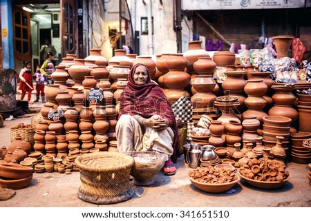 DELHI, INDIA - JANUARY 4, 2015: Indian woman selling clay pots on local market  on January 4, 2015 in Delhi, India - stock photo