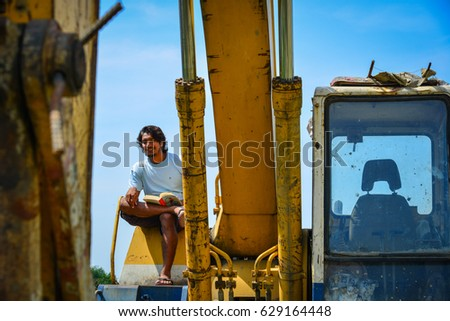 Delhi, India - Mar 9, 2017. An Indian young man reading book on the construction machine in Delhi, India.