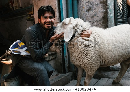 DELHI, INDIA - March 08, 2015: One unidentified man with sheep poses for a photo on the  street of Delhi in Muslim quarter