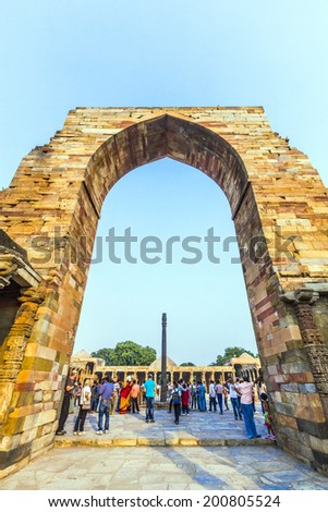 DELHI, INDIA - MARCH 27, 2012: Unidentified tourists walk around Qutub Minar complex in Delhi, India. Qutub Minar is the tallest minar in India, originally an ancient Islamic Monument.