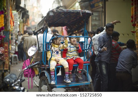 DELHI, INDIA - NOV 18: Unidentified children sit on a rickshaw in a classical street on November 18, 2012 in Delhi, India. The lifestyle in old delhi is still well kept like that in 100 years ago.  - stock photo