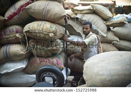 DELHI, INDIA - NOV 18: Unidentified Indian man works in a classical street in Old Delhi. November 18, 2012 in Delhi, India. The lifestyle in old delhi is still well kept like that in 100 years ago.  - stock photo