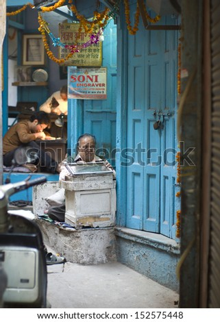 DELHI, INDIA - NOV 18: Unidentified old man works in a classical street in Old Delhi. November 18, 2012 in Delhi, India. The lifestyle in old delhi is still well kept like that in 100 years ago.  - stock photo