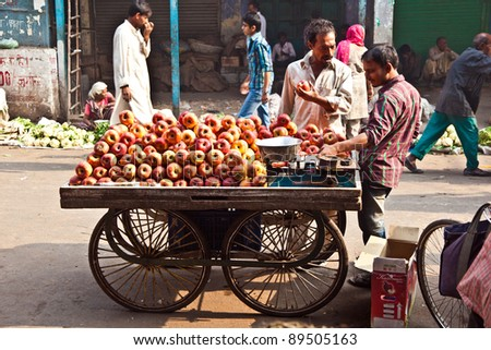 DELHI, INDIA - NOV 9: Unidentified people sell apples at Chawri Bazar on November 09, 2011 in Delhi, India. Established in 1840, with a hardware market, it was the first wholesale market of Old Delhi. - stock photo