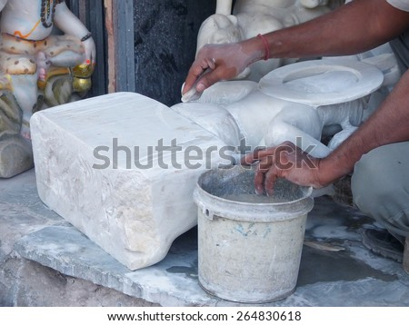 DELHI, INDIA - NOVEMBER 6: Closeup of hands of unidentified man working on a statue at a workshop on November 6, 2014 in Delhi, India. Delhi is the second most populous city in India. - stock photo