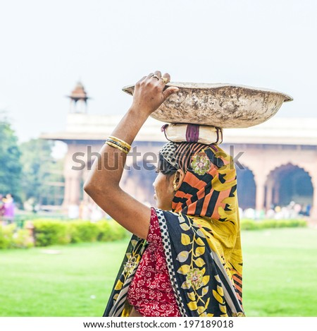 DELHI, INDIA - NOVEMBER 9, 2011: female worker carries rock waste on her hat in Delhi, India. 2,057  Mio women work in the construction business (2004) and the figures are increasing. - stock photo