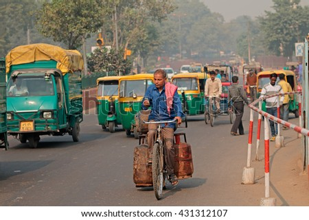 DELHI, INDIA - NOVEMBER 20, 2015: Man on a bicycle in the crowded traffic with colorful Tuk-Tuk vehicles and visible smog of air pollution