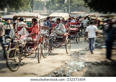 DELHI, INDIA - NOVEMBER 10: Morning on a street at November 10, 2013 in Old Delhi, India. Indian capital still uses man powered rickshaws as a usual mean of transport.  - stock photo