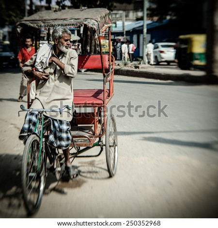 DELHI, INDIA - NOVEMBER 10: Morning on a street at November 10, 2013 in Old Delhi, India. Indian capital still uses man powered rickshaws as a usual means of transport.  - stock photo