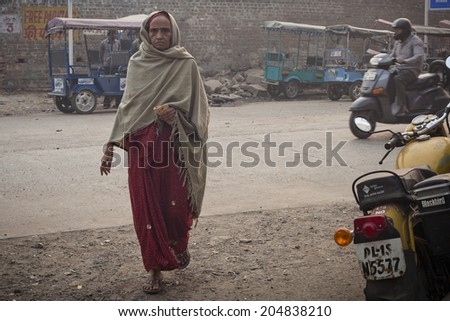DELHI, INDIA - NOVEMBER 10: Morning on a street , poor woman with roti, at November 10, 2013 in Old Delhi, India - stock photo