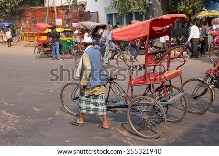 DELHI, INDIA - NOVEMBER 5: Unidentified  cycle rickshaw walks in the street on November 5, 2014 in Delhi, India. Cycle rickshaw is popular mode of travel for short distance transits in the city. - stock photo
