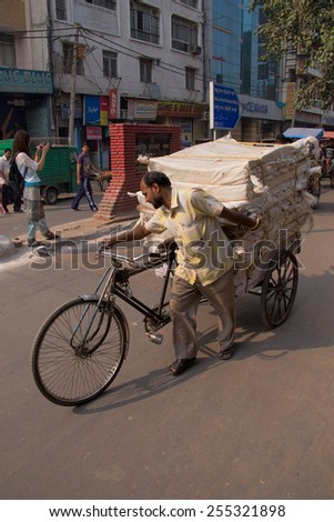 DELHI, INDIA - NOVEMBER 5: Unidentified cycle rickshaw walks with goods on November 5, 2014 in Delhi, India. Cycle rickshaw is popular mode of travel for short distance transits in the city. - stock photo