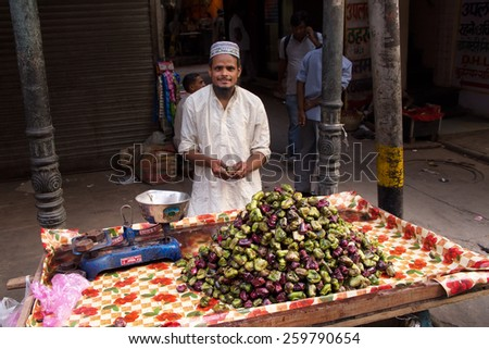 DELHI, INDIA - NOVEMBER 5: Unidentified man sells fruits from a stall on November 5, 2014 in Delhi, India. Street vendors are widely spread through out the city.  - stock photo