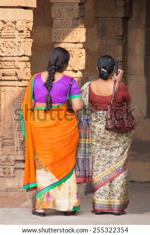 DELHI, INDIA - NOVEMBER 4: Unidentified women stand in Quwwat-Ul-Islam mosque courtyard at Qutub Minar complex on November 4, 2014 in Delhi, India. Qutub Minar is the tallest minar in India