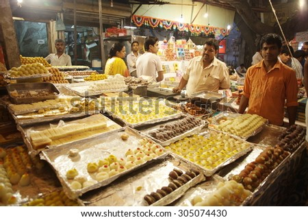 DELHI, INDIA - NOVEMBER 2:Vendors of famous indian sweets on famous Main Bazaar Road on November 2, 2013 in Delhi - stock photo
